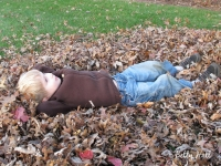 Boy lying in leaves