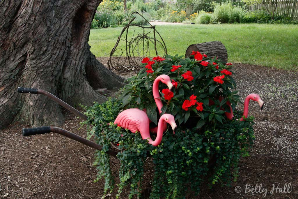 Pink plastic flamingos in wheelbarrow with flowers